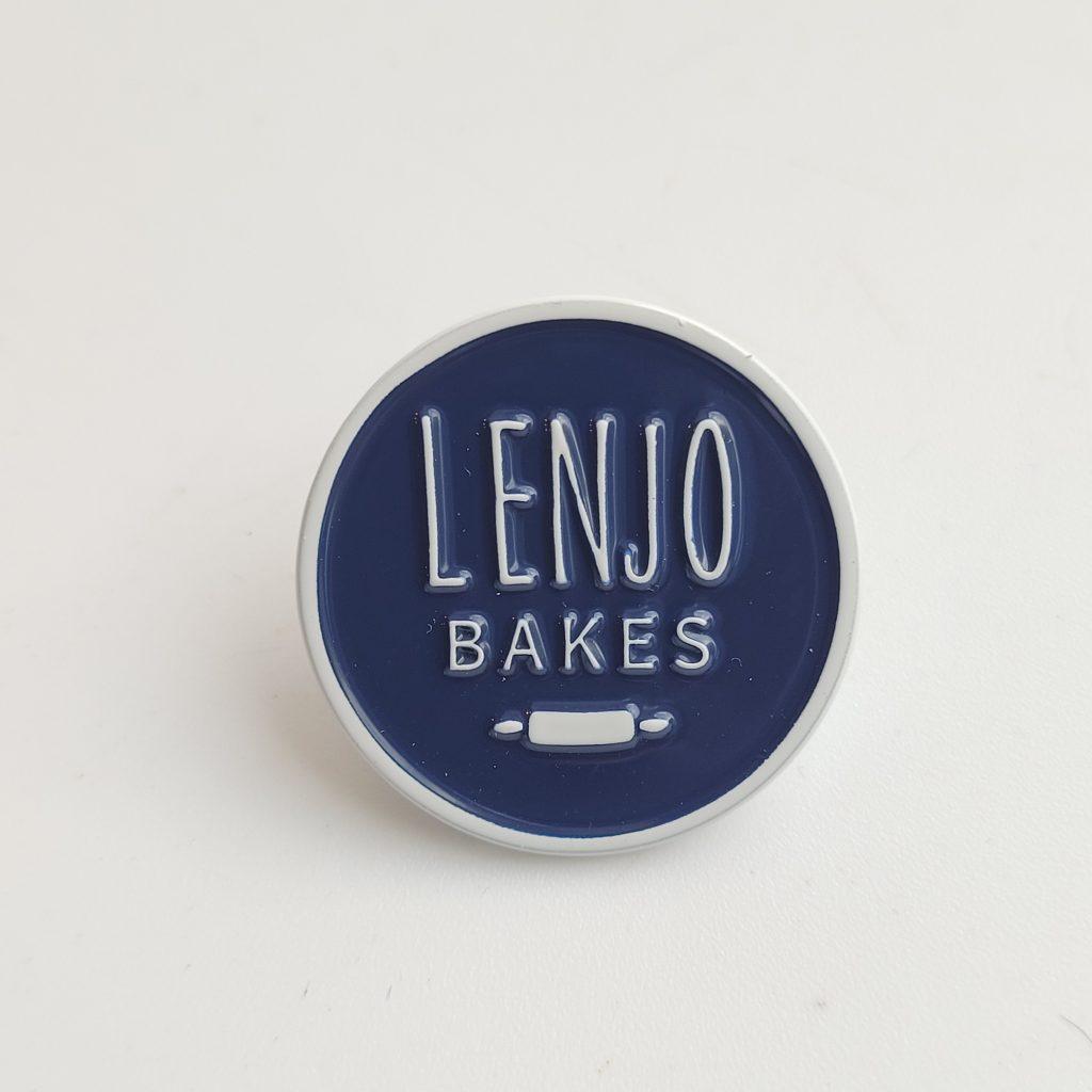 Navy enamel pin with white LenJo Bakes logo. White background.